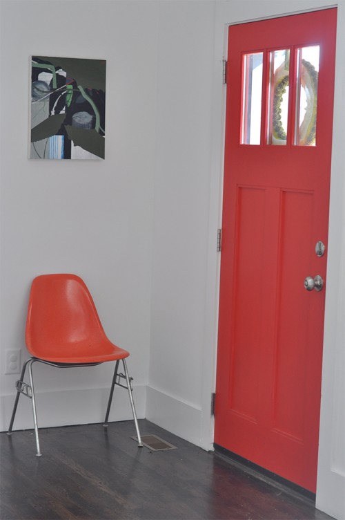 Design Sponge / Our front door is painted, front and back, with Sherwin Williams Cherry Tomato. Herman Miller vintage chair under my 2013 painting, Janky (oil on board 20 x 16).