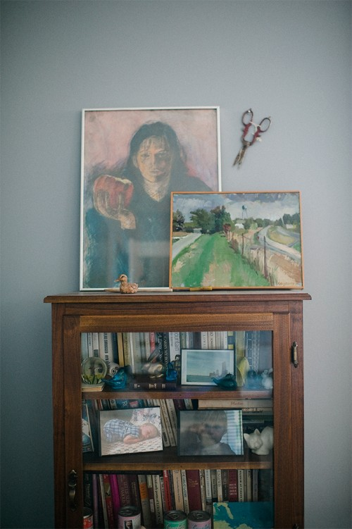 Design Sponge / This glass bookcase is a family piece in our master bedroom.  On top are a self portrait when I was attending School of Visual Arts, grandmother's sewing scissors and an Alecia Augspurg Missouri landscape.