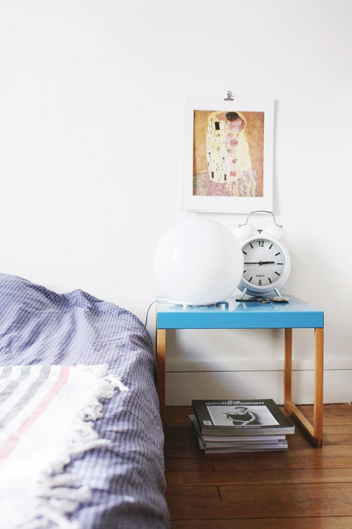 """Design Sponge/ The bedside table is by Habitat and the bed linen is from Monoprix. The print is """"The Kiss"""" by Klimt, and the pile of magazines has The Gentlewoman on the top."""