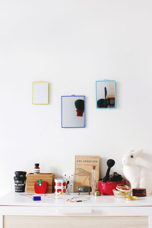 Design Sponge/ Dresser with basic colored mirrors, my favorite jewelry, an apple cup I bought in Brussels, a small jewelry box which belonged to my grandmother, a secondhand book on insects, and a nightlight rabbit.