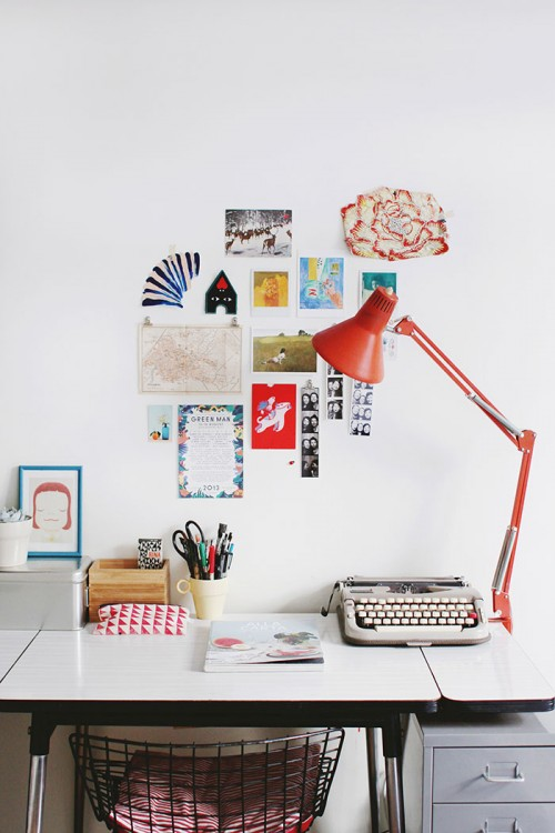 """Design Sponge/  My workspace with desk, lamp and vintage typewriter. The Diamond chair is by Harry Bertoia. The illustration in the blue frame is by Yoshitomo Nara. The pouch with red triangles is by Collectif Butane. On the wall there is an old map of Strasbourg, my hometown, photobooth photos with the friends, """"Christina's world"""" by Andrew Wyeth, and """"Poisson rouge et sculpture"""" by Henri Matisse."""