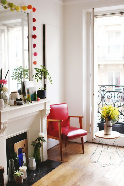 """Design Sponge/ The lounge. The vintage red armchair was given to me by a friend. Table DIY was made with an old structure of a lamp. The colored garland is by """"la Case de cousin Paul."""""""