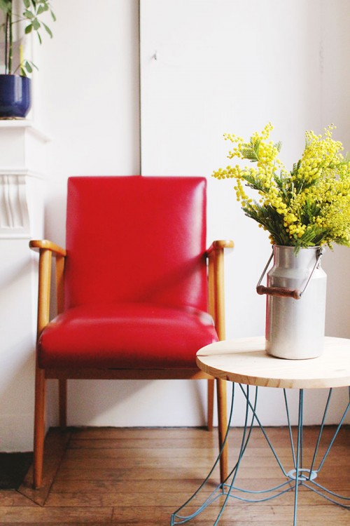 Design Sponge/ Another look at the red chair and DIY table. The vintage milk jar holds a bouquet of mimosa.