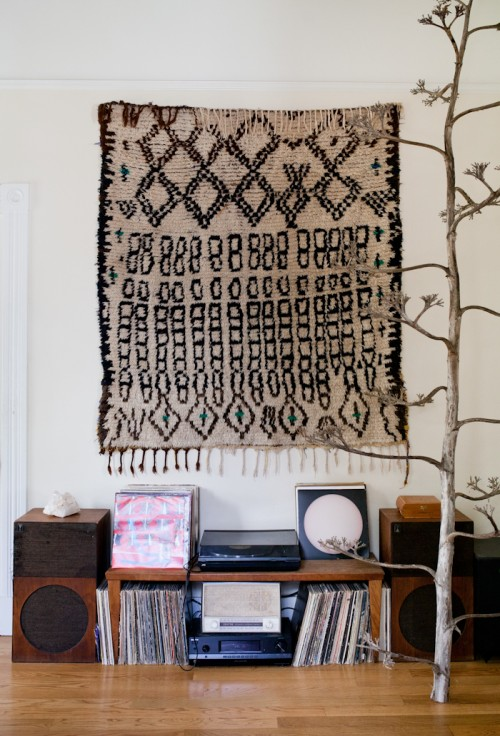 Design Sponge/ Our record player and small but growing record collection sits below a Berber Rug from Morocco on loan from our friend Gilda Hariri. The centennial plant completes the color scheme and was a gift from our farmer friend Mike Sullivan.
