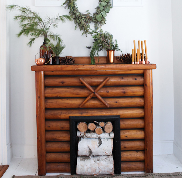 "A faux log fireplace stands on the living room's opposite wall. ""I love the warmth it brings to our home by being a central place of rest or area for watercolor painting with Lue,"" Johnna says. ""You can usually find us or the pets sprawled below here throughout the week, laying on a sheepskin. """