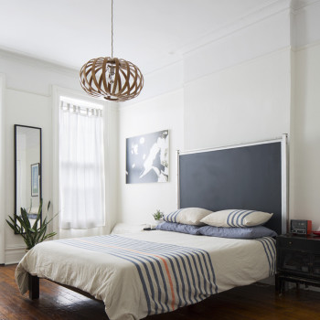 Ashima's bedroom, with its homemade headboard from a rescued chalkboard. The pendant light and bed frame are West Elm. Finally, the only successful non-succulent houseplant that has survived in Ashima's care for more than three years pokes out by the window.