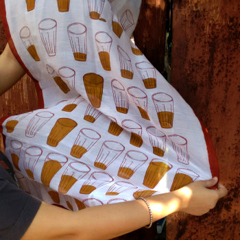 """A potent shot of chai or tea, served in small iconic glasses - commonly sold in shacks on the streets of Calcutta and across India - served as inspiration for Calcutta-based designers Syu's and Jit Art Studio's range of illustrated, block printed products, """"Cutting Chai."""""""