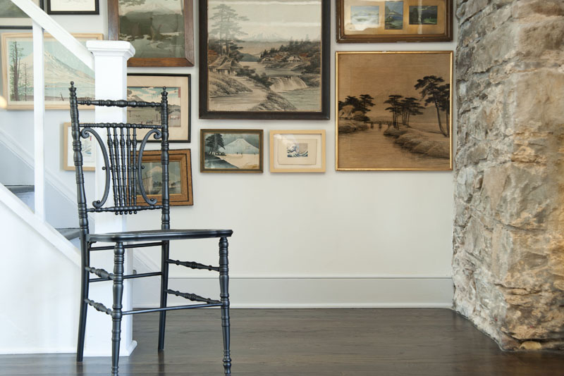 design*sponge home tour Philip Leeming and Leong Ong, vintage chair, artwork, stone wall, wood floor, dining room