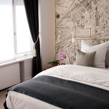 In the Calgary home of photographer Jess Loraas, a historic map of Paris was custom-printed into a large wallpaper size to anchor the wall behind her bed.
