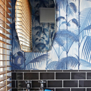 This stylish London loo feels like a tropical jungle with the addition of the classic Cole & Sons Palm Jungle wallpaper.