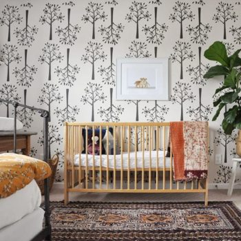 """""""I did not want to spend a lot of money on a nursery since I hoped our girls would share a room at some point, but I also wanted to make it a beautiful space to welcome my little girl,"""" homeowner Heather Jorde says. """"I worked with what I had, and only bought a few things."""" Heather achieved a high-end look on a budget with this large-scale DIY wall stencil."""
