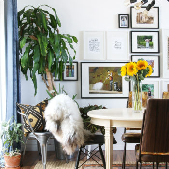 """For anyone that has ever created a gallery wall that they're proud of, you know it's quite a feat. """"It is a mix of artwork collected from our travels around the world, family photos, and personal favorites,"""" Dawnelle explains. """"The dining room table was given to me when we moved into our very first home by my mother, who originally got it from my grandmother. It is the table I remember eating Thanksgiving dinner on as a child at my grandmother's and holds a special place in my heart."""""""