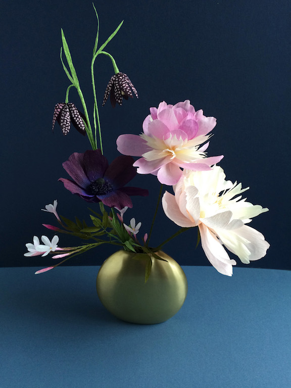 gold vase with small floral arrangement