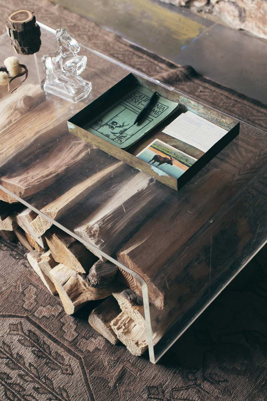 Close-Up Of Firewood Storage Beneath The Acrylic Coffee Table In This Cabin Tour On Design*Sponge