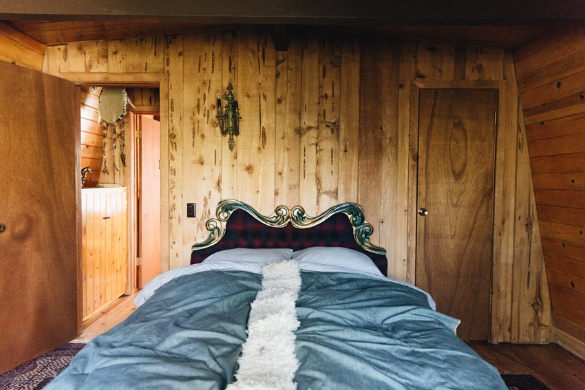 A Vintage Headboard Adds Some Regality To The Main Bedroom In This Cabin Tour On Design*Sponge
